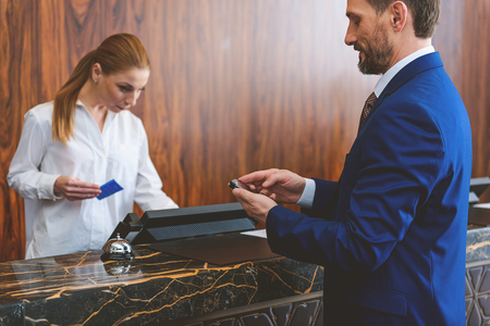 cardkey: Instantly connected to his clients. Smiling businessman checking his mobile phone at reception in hotel. Female receptionist registering customer and holding cardkey in her hand Stock Photo
