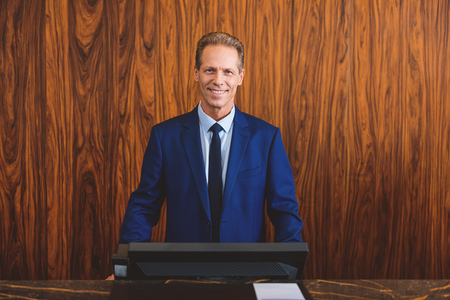 standing reception: Confident and successful leader. Smiling mature hotelier looking content while standing reception desk in lobby