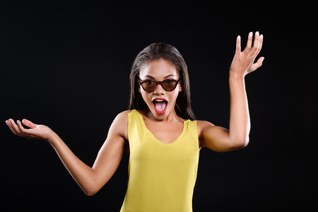 Shocked girl in sunglasses is raising her hands. She is isolated on black background Stock Photo