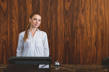 standing reception: Love what you do. Pretty young woman standing at hotel reception and looking at camera, smiling