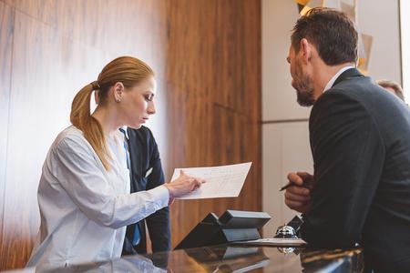 喜びでクライアントを支援します。リストに彼の名前を検索しながらホテルにチェックインする中年の男性を助ける若い女性受付