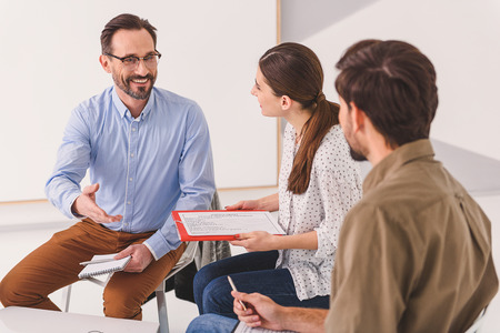 Introduce yourself. Amiable psychotherapist is asking people for introduction, while sitting at stool
