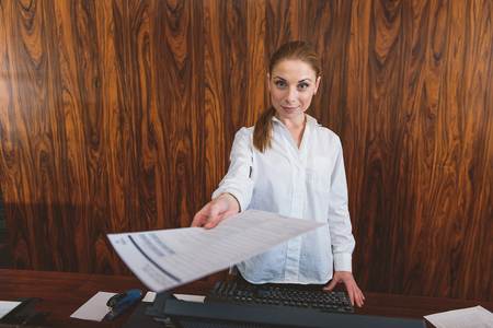 standing reception: It is your copy. Attractive hotel manager standing at reception desk and smiling at camera while offering form