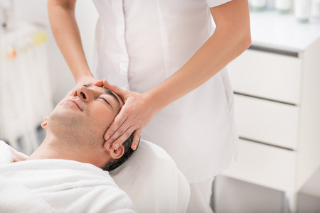 masseuse: Relaxed man is having treatment at spa. Masseuse is standing and pampering his head