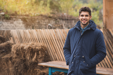 Happy young man is standing and relaxing outdoors in warm coat. He is looking at camera and smiling Stock Photo
