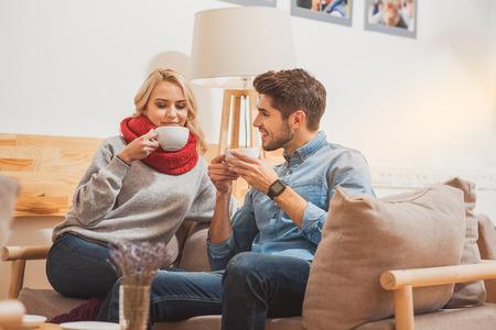 La giovane coppia amorosa allegra sta bevendo il caffè a casa. Sono seduti sul divano con il relax e sorridendo Archivio Fotografico