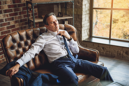 desperation: Exhausted businessman is sitting on couch and trying to take off necktie. His glance full of desperation