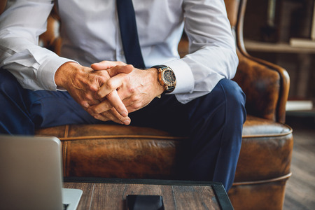 interlace: Focus on hands of businessperson. He is sitting on couch Stock Photo