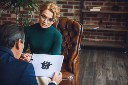 What do you see here. Serious woman is sitting afore male client. He looking at inkblot on paper Stock Photo
