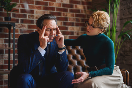 hardly: Deeply depressed businessman is sitting on sofa. He hardly massaging his head. Woman showing support Stock Photo