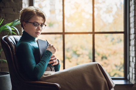 mindful: mindful female advisor is sitting on chair. She looking down, holding notepad Stock Photo