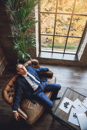 intended: Relaxing middle aged businessman is sitting on couch. He glancing up Stock Photo