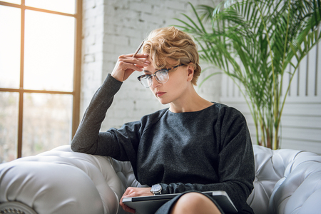 hardly: Woman sitting at armchair and hardly thinking. She keeping closed laptop on her knees, touching own forehead in stress