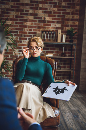 Serious female advisor is sitting on armchair. She holding tablet with inkblot and showing it to client