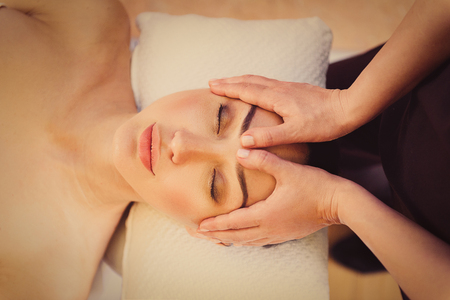 relax massage: Top view of beautician hands undergoing facial massage of young woman. Girl is lying and closed eyes with pleasure