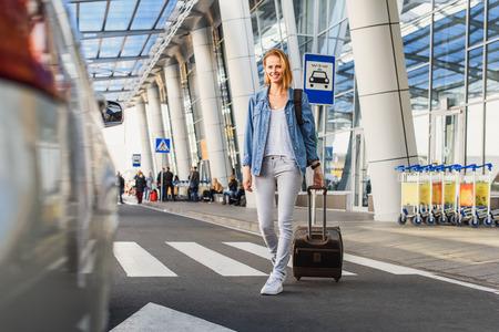 De vrolijke jonge vrouw gaat van de luchthaven taxiën. Ze draagt ??een koffer en lacht Stockfoto