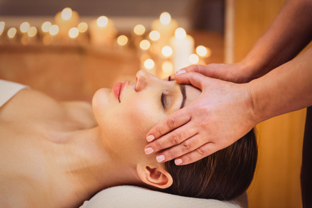 Close up of masseuse hands massaging female head. Calm young woman is lying and relaxing Stock Photo