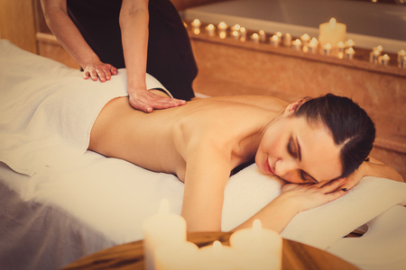 masseuse: Skillful masseuse is massaging female body. Calm young girl is relaxing at spa Stock Photo