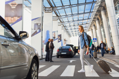 Meeting new town. Happy girl is crossing the road while arriving from airport. She is holding luggage and backpack Stock Photo