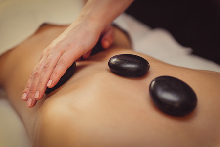 Close up of masseuse hands massaging female back by hot stones