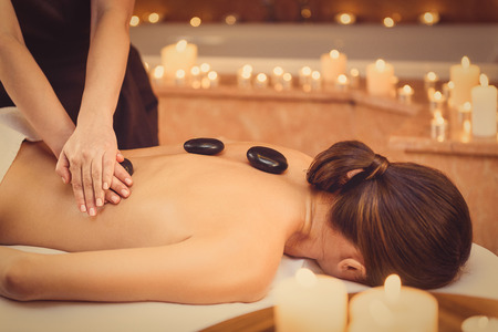 masseuse: Calm young woman is getting massage at spa. Masseuse is standing and pampering her back by stone. Candles around create relaxing atmosphere Stock Photo