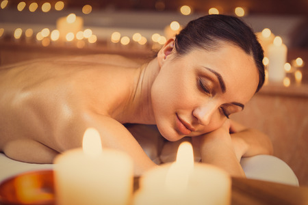 atmosphere: This is the real pleasure. Serene young girl is lying on massage table and relaxing. Candles around her create romantic atmosphere