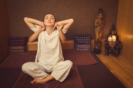 Thai massage stretch. Relaxed young woman is sitting on floor in lotus position. Masseuse is touching her arms Stock Photo