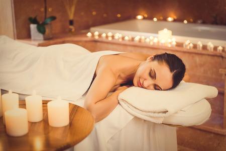 voluptuosa: Este es el verdadero placer. chica voluptuosa está durmiendo en la mesa de masaje en el spa. Velas crean un ambiente romántico