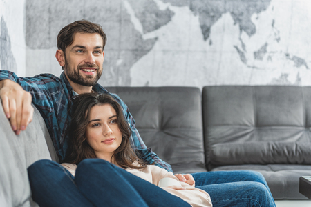 woman on couch: Young man and woman sitting on couch