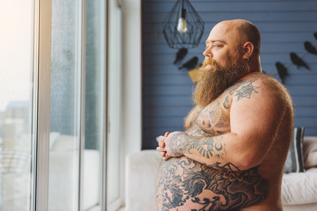Sad fat man viewing street from apartment