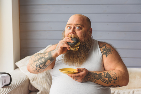 Fat man eating unhealthy burger at home