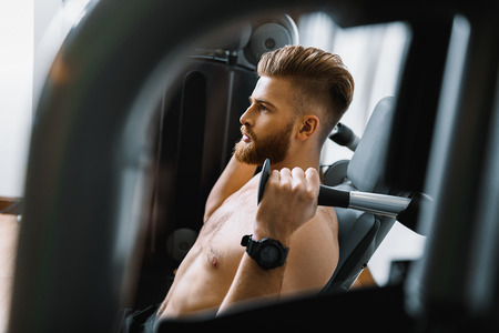assure: Confident sportsman exercising in gym Stock Photo
