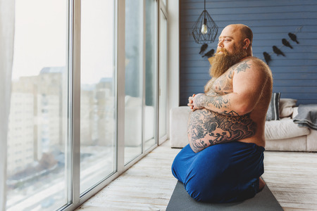 Pensive thick guy resting in apartment