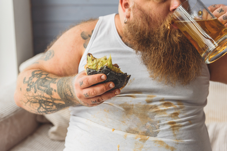 Thick male fatso enjoying beer Stock Photo