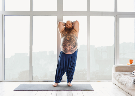 fatso: Lazy male fatso exercising in apartment