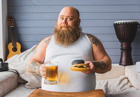unhealthy living: Fat guy eating unhealthy food