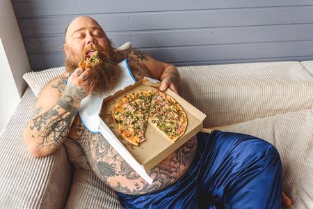 Comedor pesado masculino que morde alimentos pouco saudáveis