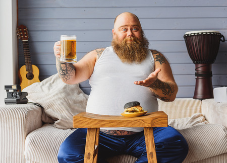 fatso: Male fatso drinking beer at home