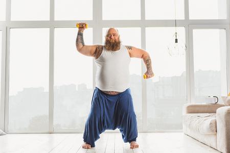 fatso: Joyful male fatso lifting weights at home Stock Photo