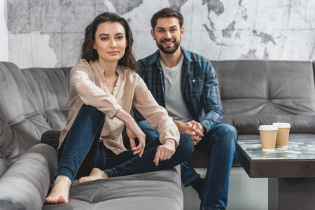 woman on couch: Joyful young man and woman relaxing on couch
