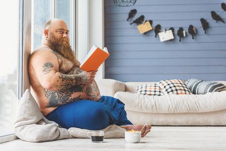 fatso: Joyful male fatso reading at home