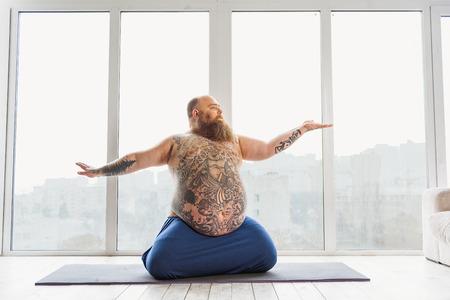 Calm fat man meditating near window Zdjęcie Seryjne