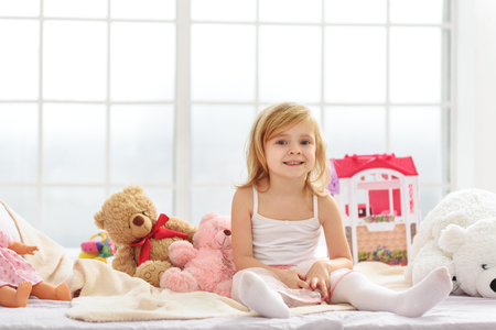 Frohes weibliches Kind, das im Schlafzimmer spielt