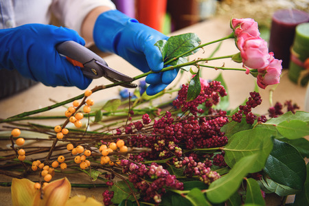 Skillful florist making bouquet in store