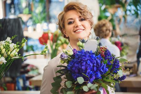 Joyful woman carrying flowers in shop