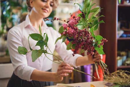 Skillful female florist enjoying her work