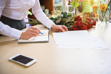 Professional florist working with documents