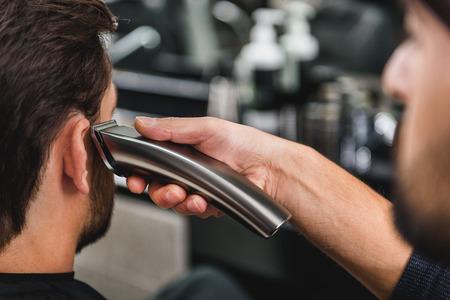 shearer: Skillful hairdresser cutting human hair by shearer
