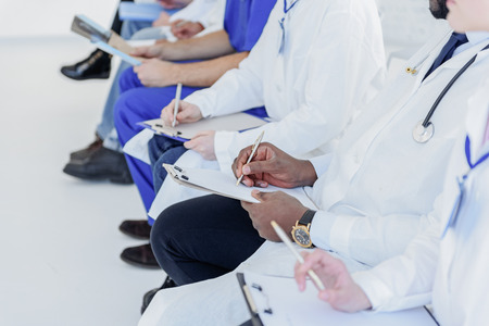 Professional general practitioners making notes at clinic