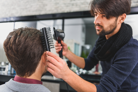 coiffeur: Concentrated hairdresser doing hairstyle with hairdryer